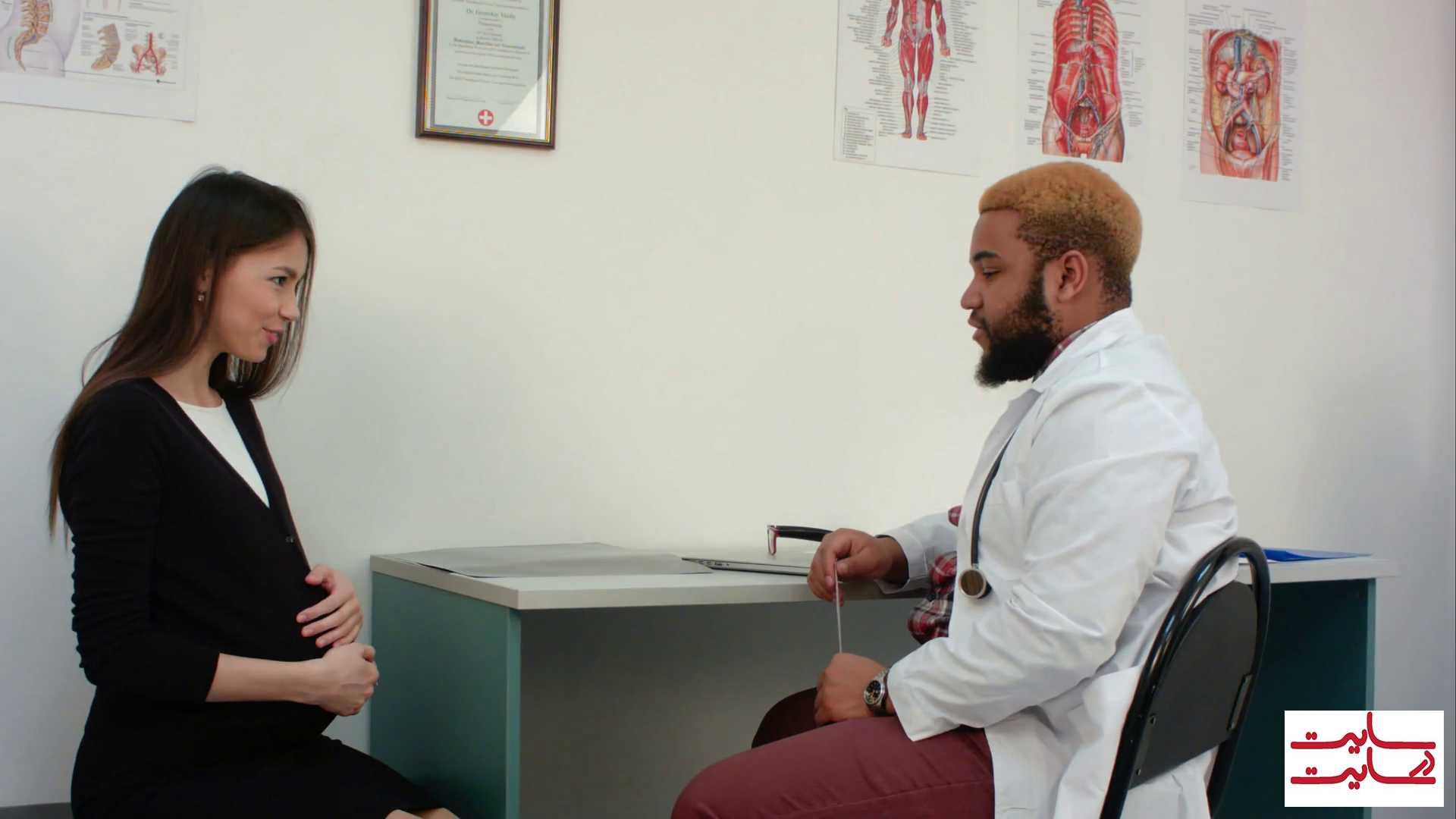 دکتر در حال صحبت کردن و راهنمایی دادن به خانم باردار